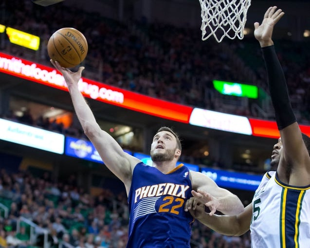 Feb 26, 2014; Salt Lake City, UT, USA; Phoenix Suns center Miles Plumlee (22) goes up for a shot against Utah Jazz center Derrick Favors (15) during the first half at EnergySolutions Arena. Mandatory Credit: Russ Isabella-USA TODAY Sports