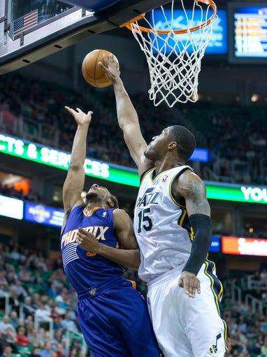 Feb 26, 2014; Salt Lake City, UT, USA; Utah Jazz center Derrick Favors (15) blocks the shot of Phoenix Suns point guard Ish Smith (3) during the first half at EnergySolutions Arena. Mandatory Credit: Russ Isabella-USA TODAY Sports