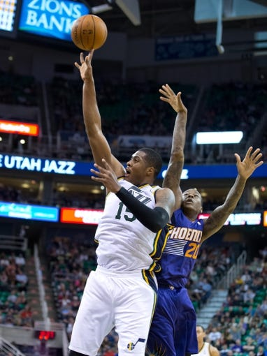 Feb 26, 2014; Salt Lake City, UT, USA; Utah Jazz center Derrick Favors (15) shoots in front of Phoenix Suns shooting guard Archie Goodwin (20) during the second half at EnergySolutions Arena. The Jazz won 109-86. Mandatory Credit: Russ Isabella-USA TODAY Sports