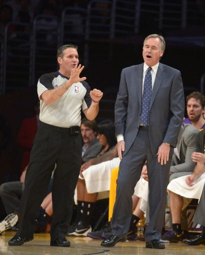 Dec 31, 2013; Los Angeles, CA, USA; Los Angeles Lakers coach Mike D'Antoni (right) reacts to a call by NBA referee Monty McCutchen (58) during the game against the Milwaukee Bucks at Staples Center. The Bucks defeated the Lakers 94-79. Mandatory Credit: Kirby Lee-USA TODAY Sports