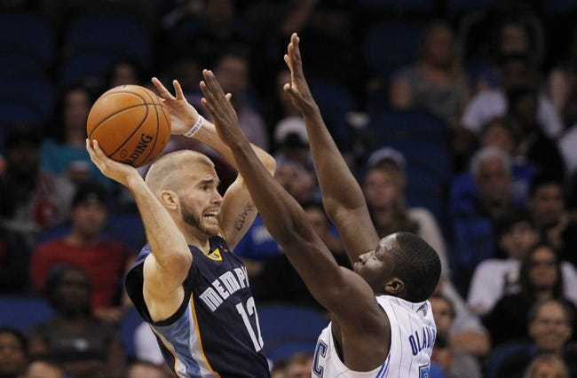 Feb 12, 2014; Orlando, FL, USA; Memphis Grizzlies shooting guard Nick Calathes (12) passes the ball over Orlando Magic shooting guard Victor Oladipo (5) during the second half at Amway Center. Memphis Grizzlies defeated the Orlando Magic 86-81. Mandatory Credit: Kim Klement-USA TODAY Sports