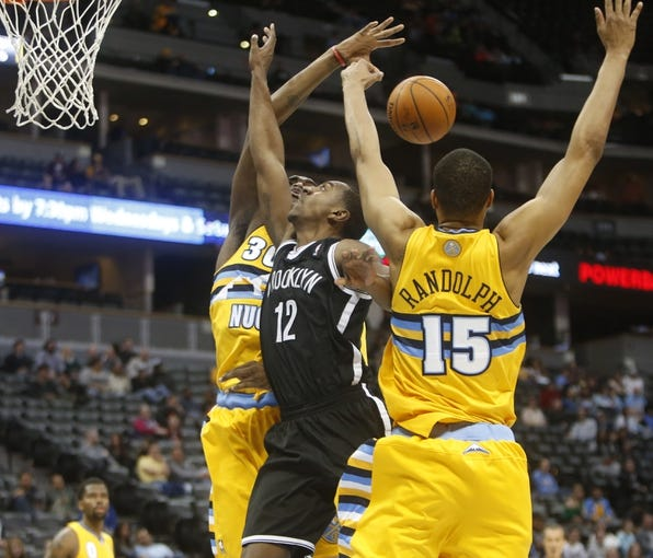 Feb 27, 2014; Denver, CO, USA; Brooklyn Nets guard Marquis Teague (12) has his shot blocked during the second half against the Denver Nuggets at Pepsi Center.  The Nets won 112-89.  Mandatory Credit: Chris Humphreys-USA TODAY Sports