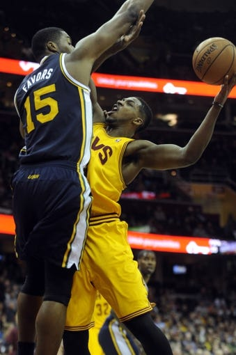 Feb 28, 2014; Cleveland, OH, USA; Cleveland Cavaliers power forward Tristan Thompson (13) drives on Utah Jazz center Derrick Favors (15) during the first quarter at Quicken Loans Arena. Mandatory Credit: Ken Blaze-USA TODAY Sports