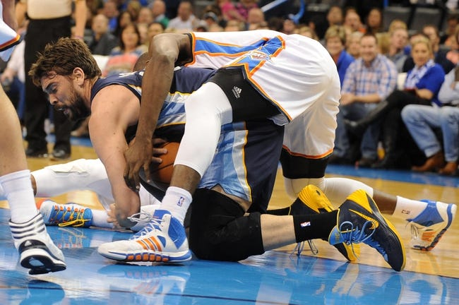 Feb 28, 2014; Oklahoma City, OK, USA; Memphis Grizzlies center Marc Gasol (33) fights for a loose ball with Oklahoma City Thunder power forward Serge Ibaka (9) during the first quarter at Chesapeake Energy Arena. Mandatory Credit: Mark D. Smith-USA TODAY Sports