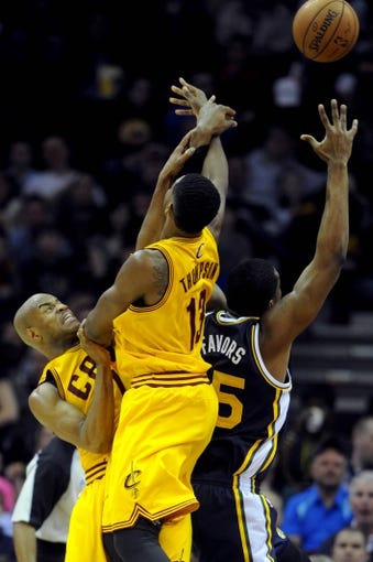 Feb 28, 2014; Cleveland, OH, USA; Cleveland Cavaliers point guard Jarrett Jack (1) and Cleveland Cavaliers power forward Tristan Thompson (13) fight for a rebound with Utah Jazz center Derrick Favors (15) during the second quarter at Quicken Loans Arena. Mandatory Credit: Ken Blaze-USA TODAY Sports