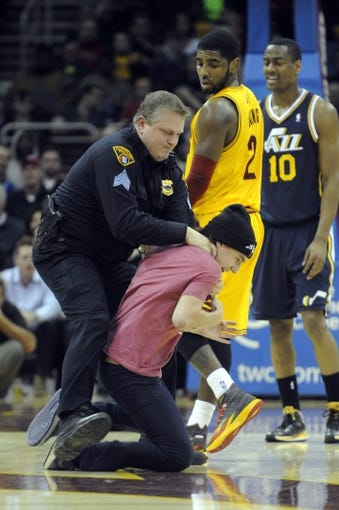 Feb 28, 2014; Cleveland, OH, USA; Cleveland Cavaliers point guard Kyrie Irving (2) and Utah Jazz point guard Alec Burks (10) watch as a Cleveland police officer tackles a fan who ran onto the floor during the fourth quarter in the game between the Cleveland Cavaliers and the Utah Jazz at Quicken Loans Arena. Mandatory Credit: Ken Blaze-USA TODAY Sports