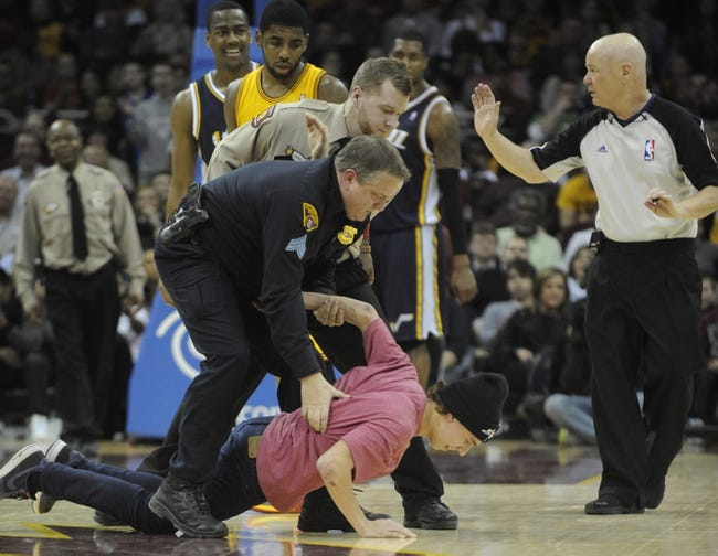 Feb 28, 2014; Cleveland, OH, USA; Cleveland police officer tackles a fan who ran onto the floor during the fourth quarter in the game between the Cleveland Cavaliers and the Utah Jazz at Quicken Loans Arena. Mandatory Credit: Ken Blaze-USA TODAY Sports