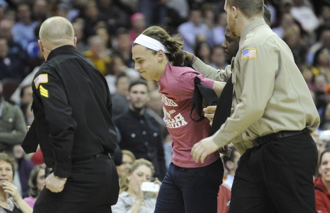 Feb 28, 2014; Cleveland, OH, USA; Cleveland police and security escort a fan from the floor after he ran out into play during the fourth quarter in the game between the Cleveland Cavaliers and the Utah Jazz at Quicken Loans Arena. Mandatory Credit: Ken Blaze-USA TODAY Sports