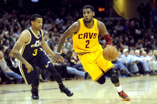 Feb 28, 2014; Cleveland, OH, USA; Cleveland Cavaliers point guard Kyrie Irving (2) drives past Utah Jazz point guard Trey Burke (3) during the second quarter at Quicken Loans Arena. The Cavaliers beat the Jazz 99-79. Mandatory Credit: Ken Blaze-USA TODAY Sports