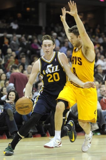 Feb 28, 2014; Cleveland, OH, USA; Utah Jazz shooting guard Gordon Hayward (20) drives on Cleveland Cavaliers shooting guard Matthew Dellavedova (8) during the fourth quarter at Quicken Loans Arena. The Cavaliers beat the Jazz 99-79. Mandatory Credit: Ken Blaze-USA TODAY Sports