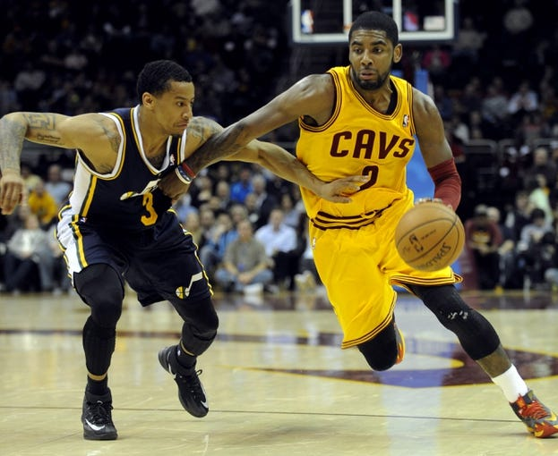 Feb 28, 2014; Cleveland, OH, USA; Cleveland Cavaliers point guard Kyrie Irving (2) drives on Utah Jazz point guard Trey Burke (3) during the second quarter at Quicken Loans Arena. The Cavaliers beat the Jazz 99-79.  Mandatory Credit: Ken Blaze-USA TODAY Sports