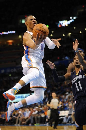 Feb 28, 2014; Oklahoma City, OK, USA; Oklahoma City Thunder point guard Russell Westbrook (0) drives to the basket against Memphis Grizzlies point guard Mike Conley (11) during the third quarter at Chesapeake Energy Arena. Mandatory Credit: Mark D. Smith-USA TODAY Sports