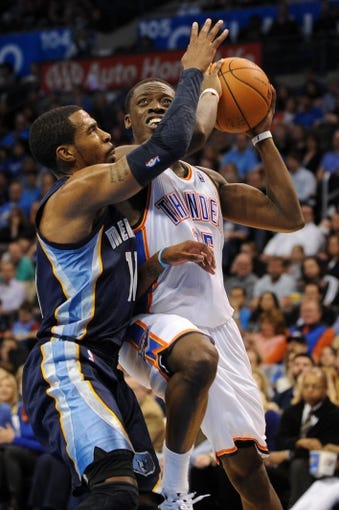 Feb 28, 2014; Oklahoma City, OK, USA; Oklahoma City Thunder point guard Reggie Jackson (15) attempts a shot against Memphis Grizzlies point guard Mike Conley (11) during the third quarter at Chesapeake Energy Arena. Mandatory Credit: Mark D. Smith-USA TODAY Sports