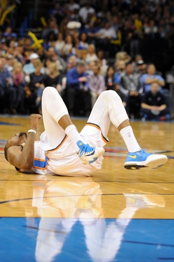 Feb 28, 2014; Oklahoma City, OK, USA; Oklahoma City Thunder small forward Kevin Durant (35) falls the floor after being fouled on a 3 point attempt in action against the Memphis Grizzlies at Chesapeake Energy Arena. Mandatory Credit: Mark D. Smith-USA TODAY Sports