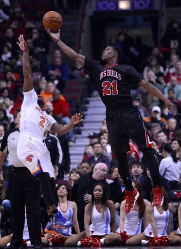 Mar 2, 2014; Chicago, IL, USA; Chicago Bulls shooting guard Jimmy Butler (21) shoots the ball against New York Knicks point guard Raymond Felton (2) during the first half at the United Center. Mandatory Credit: Mike DiNovo-USA TODAY Sports