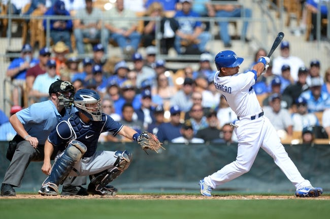 Mar 2, 2014; Phoenix, AZ, USA; Los Angeles Dodgers shortstop Alex Guerrero (7) hits the ball during the second inning against the San Diego Padres at Camelback Ranch. Mandatory Credit: Joe Camporeale-USA TODAY Sports