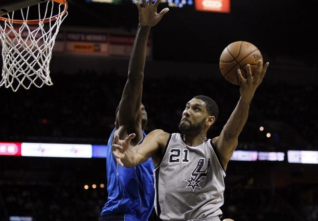 Mar 2, 2014; San Antonio, TX, USA; San Antonio Spurs forward Tim Duncan (21) shoots while being defended by Dallas Mavericks center Samuel Dalembert (1) during the first half at AT&T Center. Mandatory Credit: Soobum Im-USA TODAY Sports