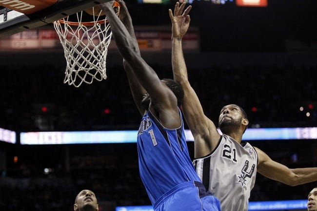 Mar 2, 2014; San Antonio, TX, USA; Dallas Mavericks center Samuel Dalembert (1) dunks past San Antonio Spurs forward Tim Duncan (21) during the second half at AT&T Center. Mandatory Credit: Soobum Im-USA TODAY Sports
