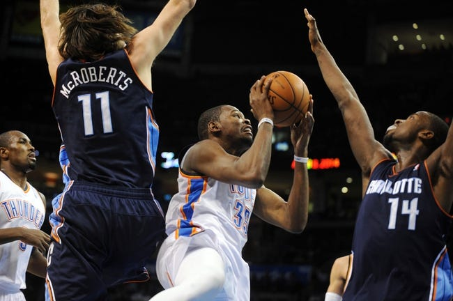 Mar 2, 2014; Oklahoma City, OK, USA; Oklahoma City Thunder small forward Kevin Durant (35) attempts a shot against Charlotte Bobcats power forward Josh McRoberts (11) and small forward Michael Kidd-Gilchrist (14) during the fourth quarter at Chesapeake Energy Arena. Mandatory Credit: Mark D. Smith-USA TODAY Sports