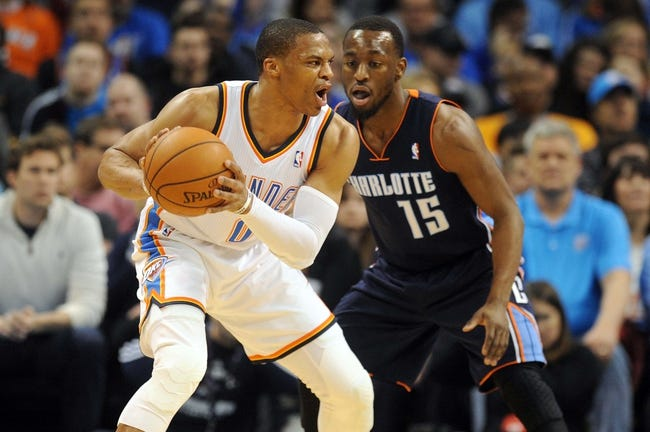 Mar 2, 2014; Oklahoma City, OK, USA; Oklahoma City Thunder point guard Russell Westbrook (0) handles the ball against Charlotte Bobcats point guard Kemba Walker (15) during the second quarter at Chesapeake Energy Arena. Mandatory Credit: Mark D. Smith-USA TODAY Sports