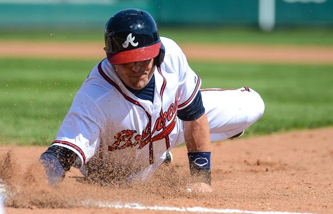 Mar 3, 2014; Lake Buena Vista, FL, USA; Atlanta Braves infielder Tyler Greene (7) dives back to first base during the spring training exhibition game against the New York Mets at Champion Stadium. Mandatory Credit: Jonathan Dyer-USA TODAY Sports