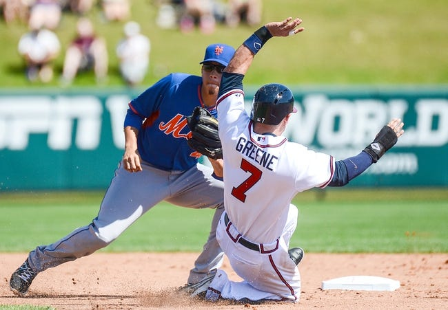 Mar 3, 2014; Lake Buena Vista, FL, USA; Atlanta Braves infielder Tyler Greene (7) tries to avoid the tag of New York Mets second basemen Wilmer Flores (4) during the spring training exhibition game at Champion Stadium. Mandatory Credit: Jonathan Dyer-USA TODAY Sports