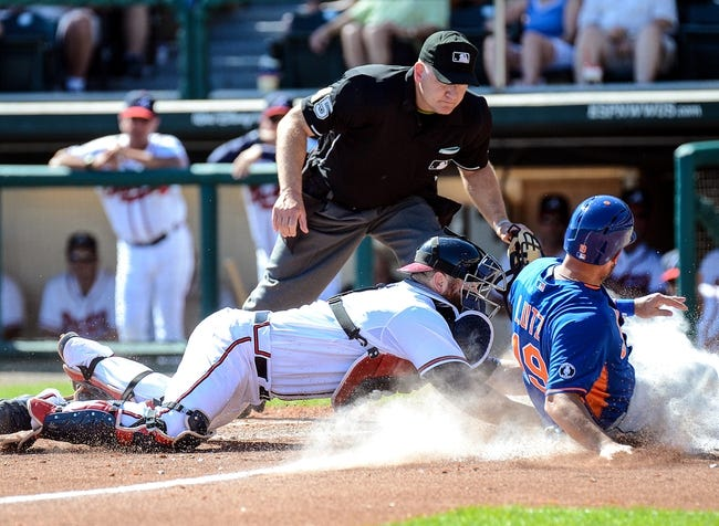 Mar 3, 2014; Lake Buena Vista, FL, USA; Atlanta Braves catcher Ryan Doumit (4) tags out New York Mets third basemen Zach Lutz (19) during the spring training exhibition game against the New York Mets at Champion Stadium. Mandatory Credit: Jonathan Dyer-USA TODAY Sports