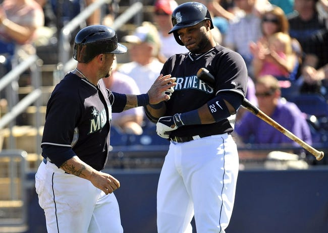 March 3, 2014; Peoria, AZ, USA; Seattle Mariners catcher Humberto Quintero (35) is greeted at home plate by second baseman Robinson Cano (22) after scoring a run in the fifth inning against the Colorado Rockies at Peoria Sports Complex. Mandatory Credit: Gary A. Vasquez-USA TODAY Sports