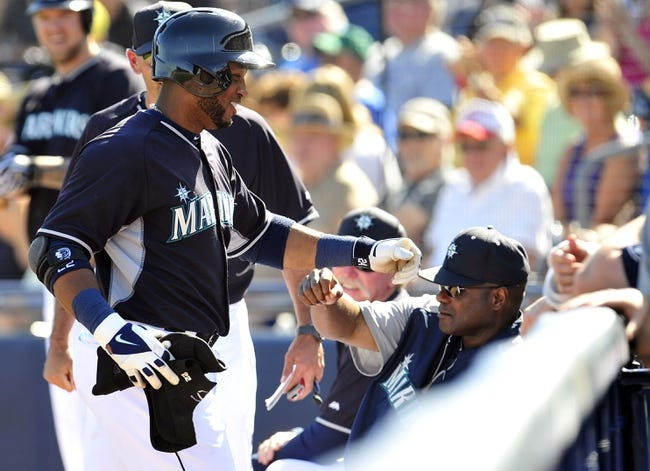 March 3, 2014; Peoria, AZ, USA; Seattle Mariners second baseman Robinson Cano (22) is greeted by manager Lloyd McClendon (23) after hitting an RBI single in the fifth inning against the Colorado Rockies at Peoria Sports Complex. Mandatory Credit: Gary A. Vasquez-USA TODAY Sports