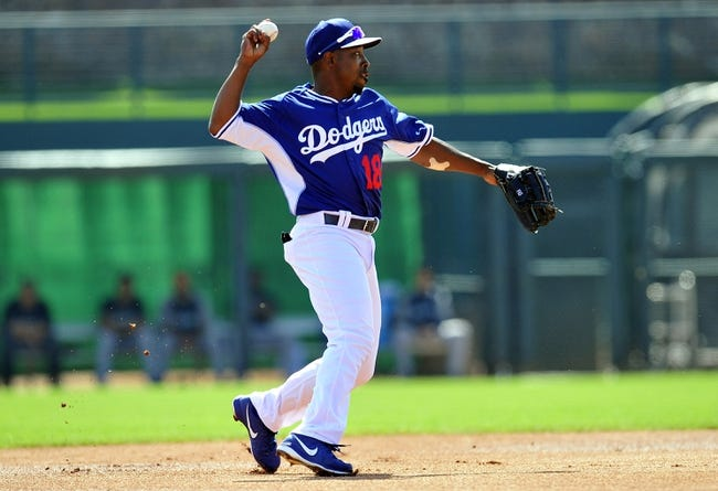 March 4, 2014; Phoenix, AZ, USA; Los Angeles Dodgers infielder Chone Figgins (18) throws to complete an out in the first inning against the Seattle Mariners at Camelback Ranch. Mandatory Credit: Gary A. Vasquez-USA TODAY Sports