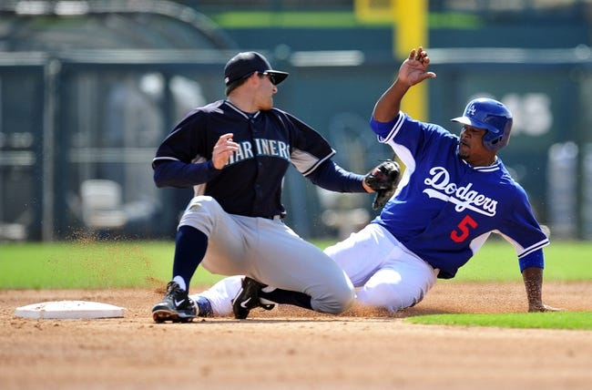 March 4, 2014; Phoenix, AZ, USA; Los Angeles Dodgers third baseman Juan Uribe (5) reaches second base on a wild pitch against the tag of Seattle Mariners shortstop Brad Miller (5) at Camelback Ranch. Mandatory Credit: Gary A. Vasquez-USA TODAY Sports