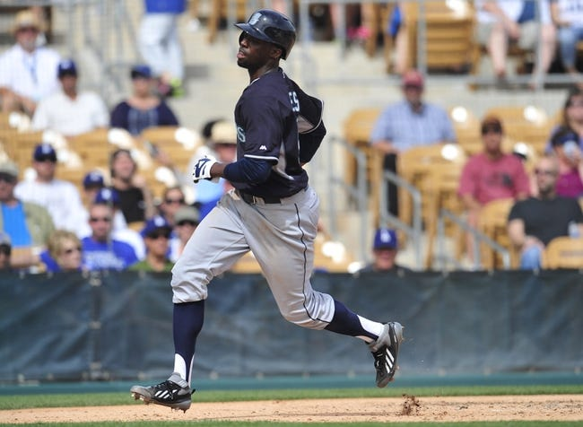 March 4, 2014; Phoenix, AZ, USA; Seattle Mariners right fielder James Jones (99) reaches home to score a run in the fourth inning against the Los Angeles Dodgers at Camelback Ranch. Mandatory Credit: Gary A. Vasquez-USA TODAY Sports