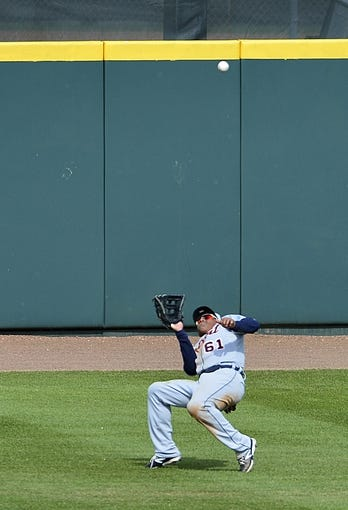 Mar 5, 2014; Kissimmee, FL, USA;  Detroit Tigers left fielder Ezequiel Carrera (61) falls back to catch a fly ball fifth inning against the Houston Astros at Osceola County Stadium. Mandatory Credit: Tommy Gilligan-USA TODAY Sports