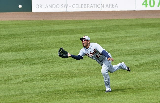 Mar 5, 2014; Kissimmee, FL, USA;  Detroit Tigers left fielder Ezequiel Carrera (61) dives to make a catch during the fifth inning against the Houston Astros at Osceola County Stadium. Mandatory Credit: Tommy Gilligan-USA TODAY Sports
