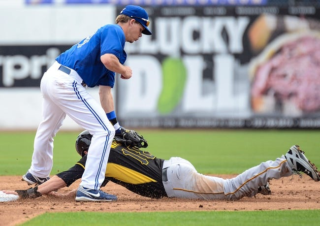 Mar 5, 2014; Dunedin, FL, USA; Pittsburg Pirates DH Neil Walker (18) slides under the tag of Toronto Blue Jays infielder Chris Getz (39) during the spring training exhibition game at Florida Auto Exchange Park. Mandatory Credit: Jonathan Dyer-USA TODAY Sports