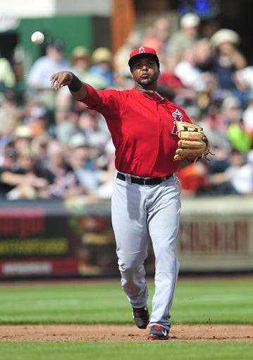March 5, 2014; Scottsdale, AZ, USA; Los Angeles Angels third baseman Luis Jimenez (13) throws to first to complete an out against the San Francisco Giants  at Scottsdale Stadium. Mandatory Credit: Gary A. Vasquez-USA TODAY Sports