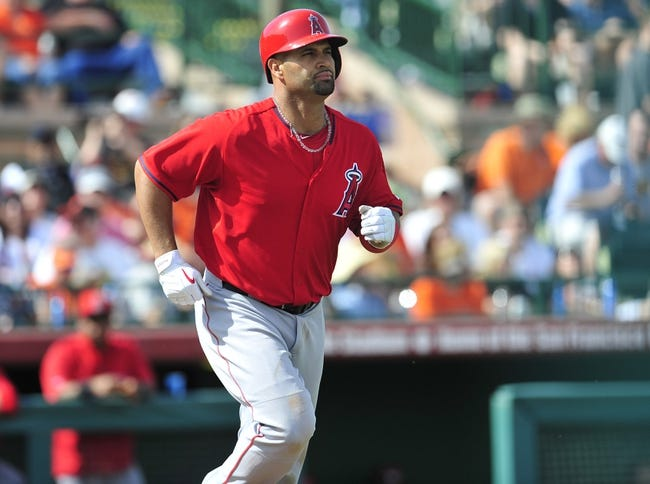March 5, 2014; Scottsdale, AZ, USA; Los Angeles Angels first baseman Albert Pujols (5) walks to first against the San Francisco Giants  at Scottsdale Stadium. Mandatory Credit: Gary A. Vasquez-USA TODAY Sports