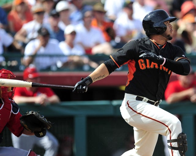 March 5, 2014; Scottsdale, AZ, USA; San Francisco Giants center fielder Gregor Blanco (7) hits a single in the third inning against the Los Angeles Angels at Scottsdale Stadium. Mandatory Credit: Gary A. Vasquez-USA TODAY Sports