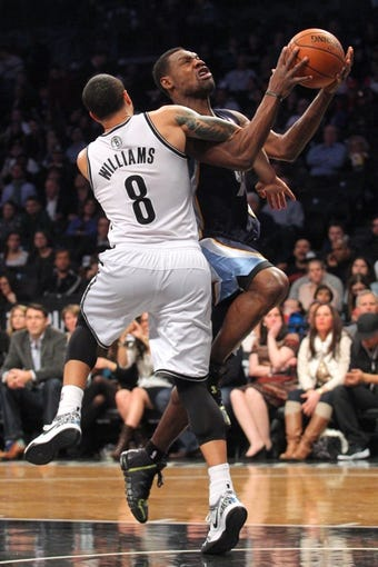 Mar 5, 2014; Brooklyn, NY, USA; Memphis Grizzlies shooting guard Tony Allen (9) is fouled by Brooklyn Nets point guard Deron Williams (8) as he drives to the basket during the second quarter of a game at Barclays Center. Mandatory Credit: Brad Penner-USA TODAY Sports