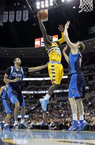 Mar 5, 2014; Denver, CO, USA; Denver Nuggets power forward J.J. Hickson (7) takes a shot against Dallas Mavericks power forward Dirk Nowitzki (41) and power forward Brandan Wright (34) in the second quarter at the Pepsi Center. Mandatory Credit: Isaiah J. Downing-USA TODAY Sports