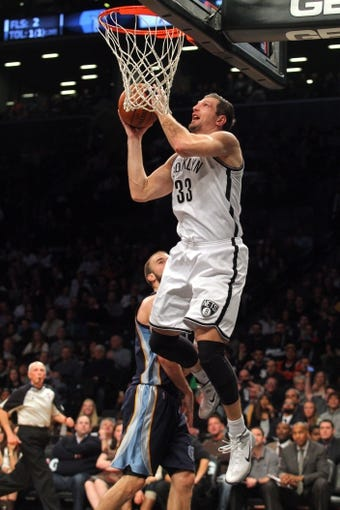 Mar 5, 2014; Brooklyn, NY, USA; Brooklyn Nets power forward Mirza Teletovic (33) drives to the basket against Memphis Grizzlies shooting guard Nick Calathes (12) during the fourth quarter of a game at Barclays Center. The Nets defeated the Grizzlies 103-94. Mandatory Credit: Brad Penner-USA TODAY Sports