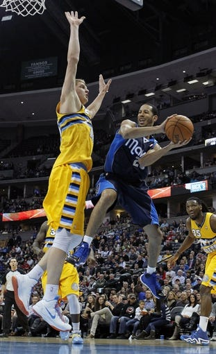 Mar 5, 2014; Denver, CO, USA; Dallas Mavericks point guard Devin Harris (20) looks to make a pass around Denver Nuggets center Timofey Mozgov (25) in the third quarter at the Pepsi Center. The Nuggets won 115-110. Mandatory Credit: Isaiah J. Downing-USA TODAY Sports