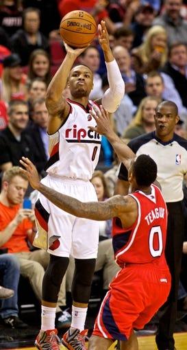 Mar 5, 2014; Portland, OR, USA; Portland Trail Blazers point guard Damian Lillard (0) shoots a three point basket over Atlanta Hawks point guard Jeff Teague (0) at the Moda Center. Mandatory Credit: Craig Mitchelldyer-USA TODAY Sports