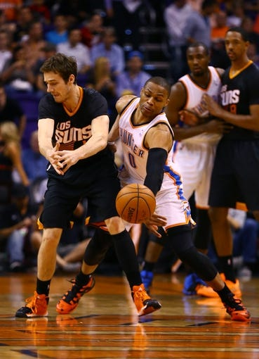Mar 6, 2014; Phoenix, AZ, USA; Oklahoma City Thunder guard Russell Westbrook (right) steals the ball from Phoenix Suns guard Goran Dragic in the first quarter at the US Airways Center. Mandatory Credit: Mark J. Rebilas-USA TODAY Sports