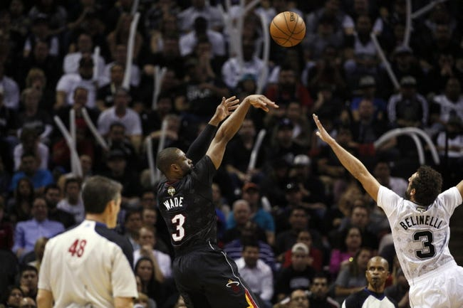 Mar 6, 2014; San Antonio, TX, USA; Miami Heat guard Dwyane Wade (3) shoots the ball over San Antonio Spurs forward Marco Belinelli (3) during the second half at AT&T Center. The Spurs won 111-87. Mandatory Credit: Soobum Im-USA TODAY Sports