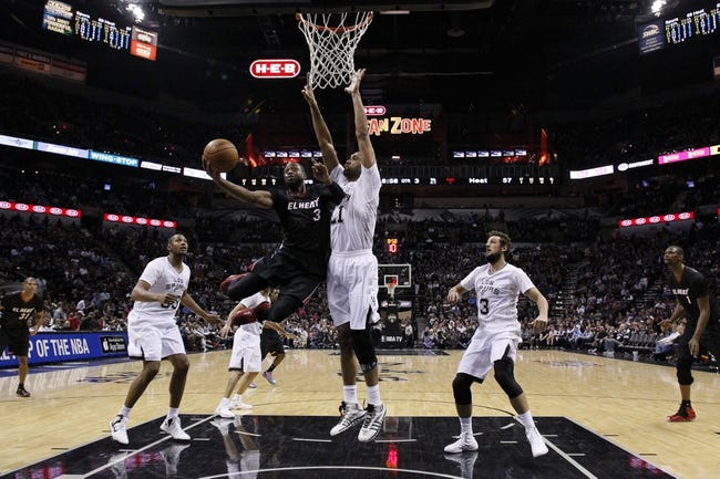 Mar 6, 2014; San Antonio, TX, USA; Miami Heat guard Dwyane Wade (3) shoots the ball as San Antonio Spurs forward Tim Duncan (21)  defends during the second half at AT&T Center. The Spurs won 111-87. Mandatory Credit: Soobum Im-USA TODAY Sports