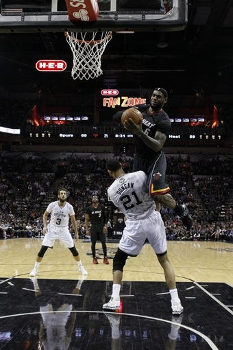Mar 6, 2014; San Antonio, TX, USA; San Antonio Spurs forward Tim Duncan (21) draws a charge from Miami Heat forward LeBron James (6) during the second half at AT&T Center. The Spurs won 111-87. Mandatory Credit: Soobum Im-USA TODAY Sports