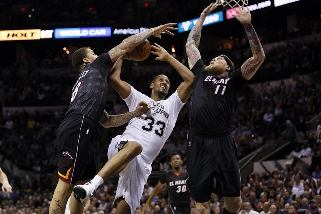 Mar 6, 2014; San Antonio, TX, USA; San Antonio Spurs forward Boris Diaw (33) gets fouled while shooting against Miami Heat forward Michael Beasley (8) during the second half at AT&T Center. The Spurs won 111-87. Mandatory Credit: Soobum Im-USA TODAY Sports