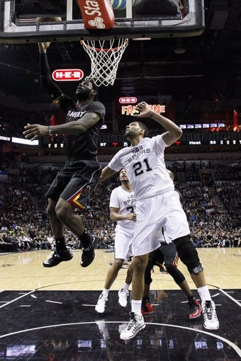 Mar 6, 2014; San Antonio, TX, USA; Miami Heat forward LeBron James (top) shoots the ball past San Antonio Spurs forward Tim Duncan (21) during the second half at AT&T Center. The Spurs won 111-87. Mandatory Credit: Soobum Im-USA TODAY Sports