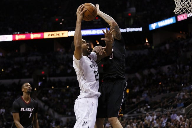Mar 6, 2014; San Antonio, TX, USA; San Antonio Spurs forward Tim Duncan (left) shoots the ball as Miami Heat forward Michael Beasley (right) defends during the second half at AT&T Center. The Spurs won 111-87. Mandatory Credit: Soobum Im-USA TODAY Sports
